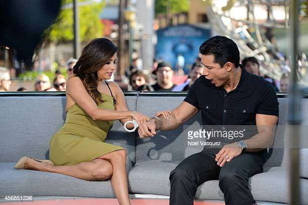 Eva Longoria puts handcuffs on Mario Lopez at 'Extra' at Universal Studios Hollywood on October 8 2014 in Universal City California