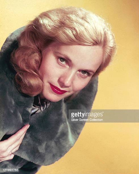 Eva Marie Saint US actress wearing a grey fur stole in a studio portrait against a yellow background circa 1955
