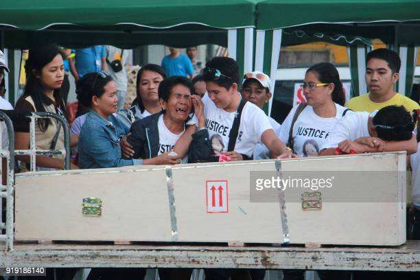 Eva mother of Filipina worker Joanna Demafelis whose body was found inside a freezer in Kuwait cries in front of the wooden casket containing her...