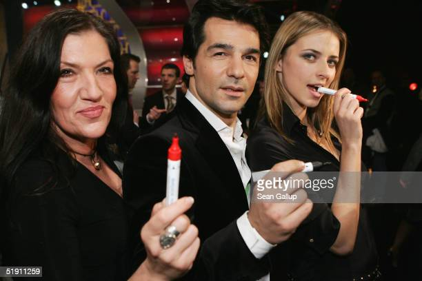 Eva Padberg Katy Karrenbauer and Erol Sander hold their pens after signing a PT Cruiser after the live broadcast of the SAT1 telethon benefit Germany...