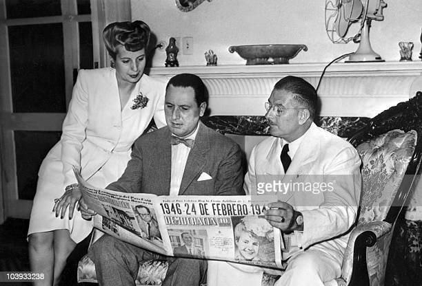 Eva Peron and her husband Argentine President Juan Peron and Colonel Mercante read in Buenos Aires Democracia issue of 24 February 1946 the election...