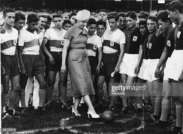 Eva Peron former actress and wife of Argentinian President Juan Peron and commonly known as Evita takes the first kick in a football match She stands...