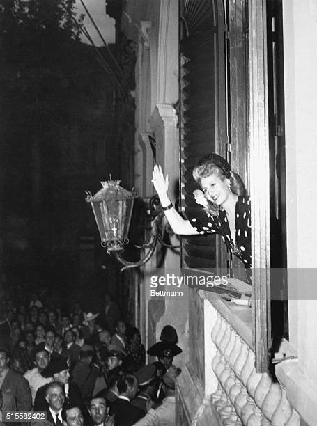 Eva Peron waves from her room in the Argentine Embassy to cheering crowds below