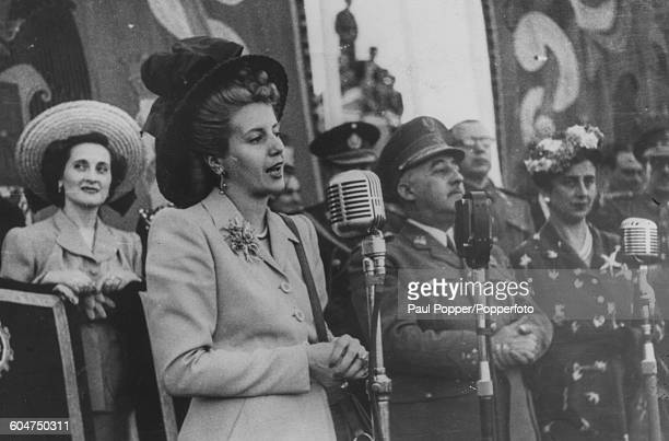 Eva Peron wife of President of Argentina Juan Peron speaks in to a microphone at the Festival of the Virgin of Paloma with General Francisco Franco...