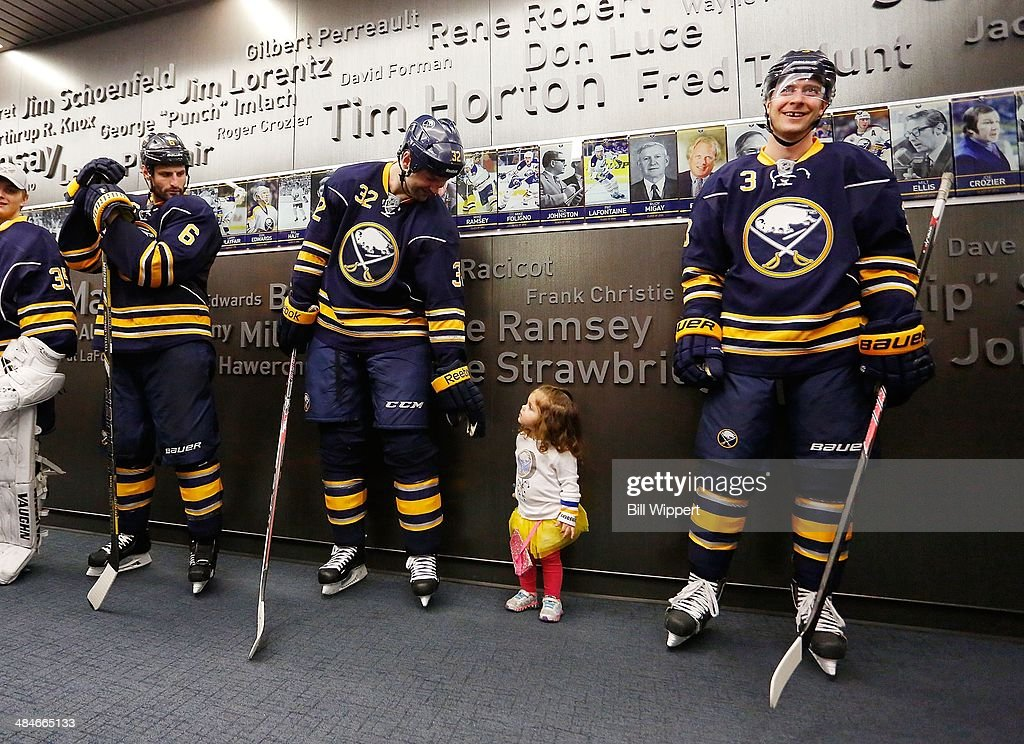Eva Scott, 2, holds hands with her father, John Scott #32 of the Buffalo Sabres, before the third period of a game against the New York Islanders on April 13, 2014 at the First Niagara Center in Buffalo, New York. Standing alongside are Mike Weber #6 and Mark Pysyk #3 of the Sabres.