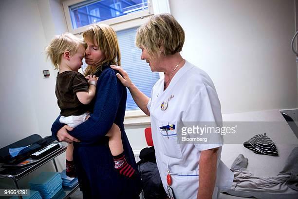 Eva Segerstedt holds her son Robin as nurse Marianne Widergren attends to them at the emergency unit of Astrid Lindgren's Children's Hospital in...