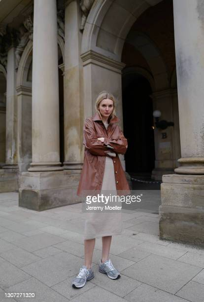 Eva Staudinger wearing beige SoSUE oversized midi dress, brown leather jacket and grey New Balance sneakers on March 07, 2021 in Hamburg, Germany.