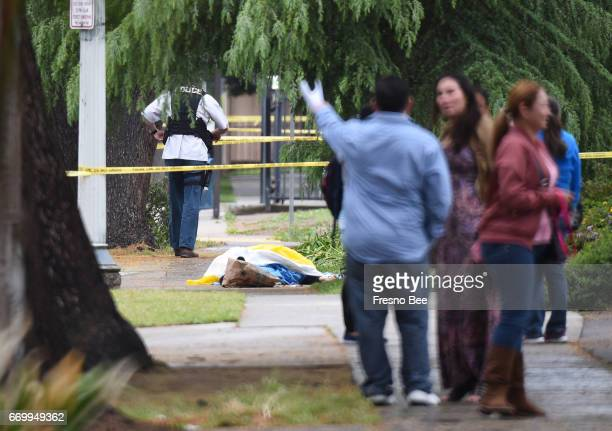 Evacuated office workers stand by with the deceased shooting victim down the sidewalk on Fulton Street north of Nevada Avenue on Tuesday morning...