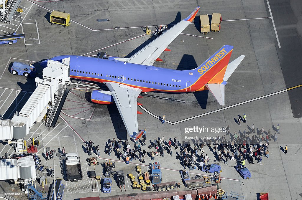 Evacuated passengers wait on the tarmac next to a Southwest Airlines passenger jet after a shooting at Los Angeles International Airport November 1, 2013 in Los Angeles, California. A man reportedly pulled an assault rifle in Terminal 3 of teh airport and shot his way through security, killing one Transportation Security Administration (TSA) worker and wounding several others.