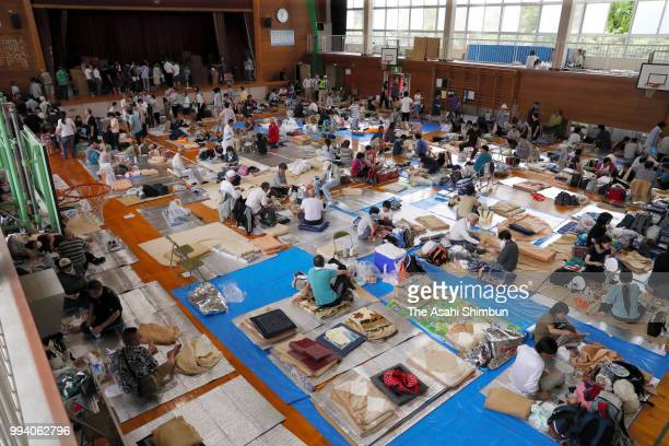 Evacuated people rest at Okada Elementary School where they take shelter as the Mabicho area is submerged after heavy rain on July 8 2018 in...