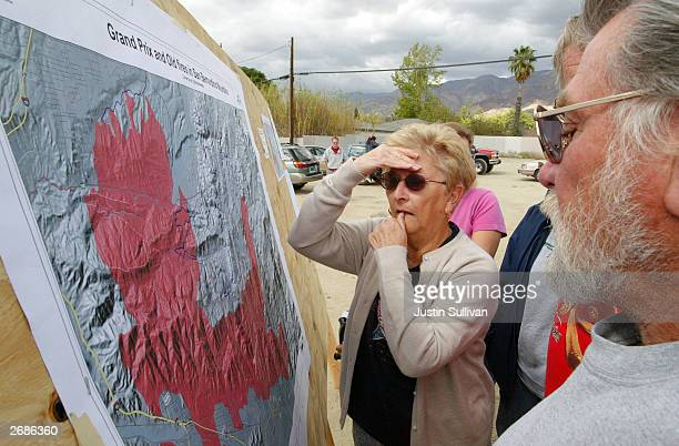 Evacuated resident Joanne Vaiana of Crestline California looks at a map of areas affected by a raging wildfire October 31 2003 in San Bernardino...