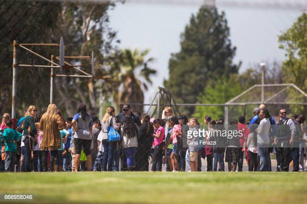 Evacuated students and teachers gather on the playground after a shooting inside North Park Elementary School on April 10 2017 in San Bernardino...