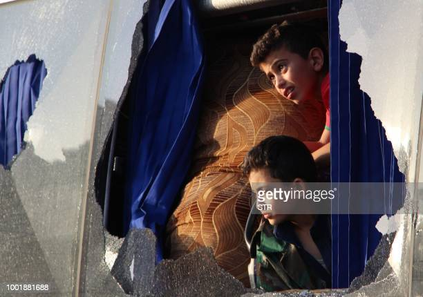 Evacuated Syrian boys from the area of Fuaa and Kafraya in the Idlib province look out of a broken bus window as it passes the alEis crossing south...