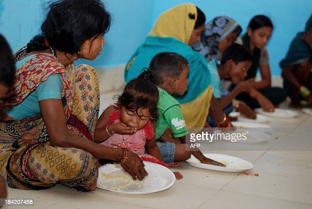 Evacuated villagers eat their midday meal at a relief camp in Berhampur city about 180 kilometers south of eastern city Bhubaneswar on October 12...