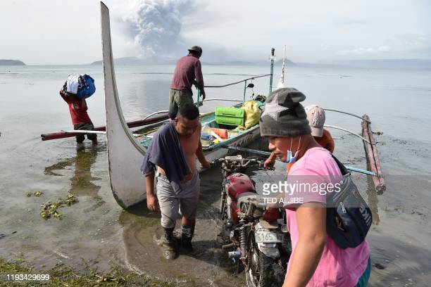 Evacuating residents living at the foot of Taal volcano unload their belongings from an outrigger canoe while the volcano spews ash as seen from...