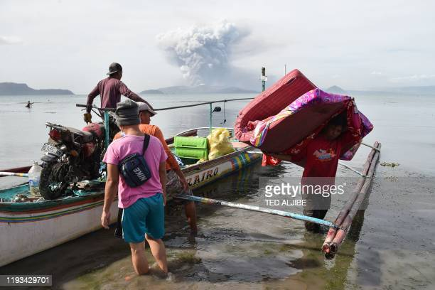 TOPSHOT Evacuating residents living at the foot of Taal volcano unload their belongings from an outrigger canoe while the volcano spews ash as seen...