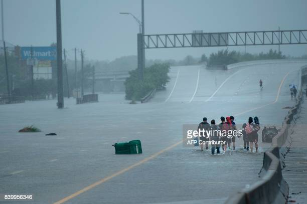 Evacuation residents from the Meyerland area walk onto an I-610 overpass for further help during the aftermath of Hurricane Harvey August 27, 2017 in...