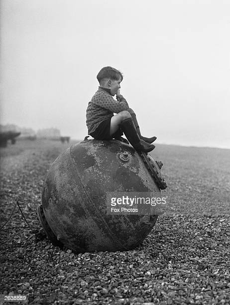 Evacuee Barrie Peacop enjoys an ice cream as he sits on a mine washed up on the beach at Deal in Kent 7th February 1940