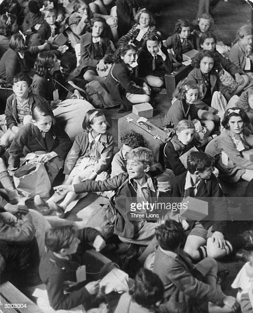 Evacuee children sitting on the ground with their luggage and gas masks in cardboard boxes slung round their necks The children, from London, are at...