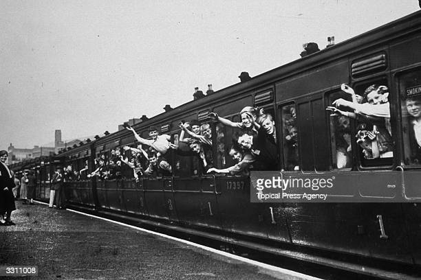 Evacuee children waving from a train as they leave London