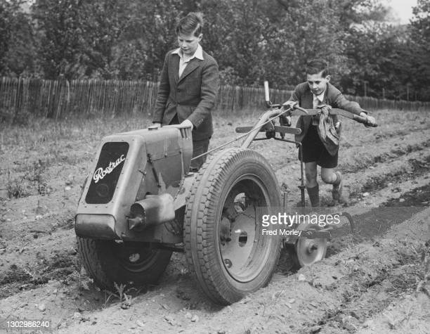 Evacuee schoolboys from London at work using a motorised Rowtrac harrowing machine on the grounds of the Ashley House School for the Dig for Victory...