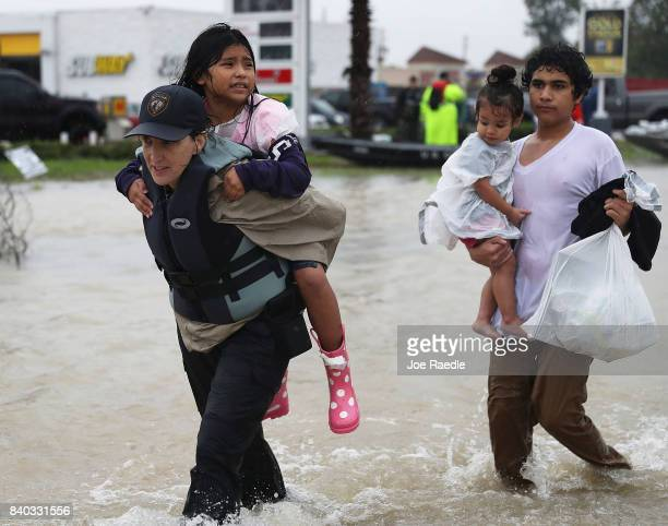 Evacuees are helped to dry land after their homes were inundated with flooding from Hurricane Harvey on August 28 2017 in Houston Texas Harvey which...