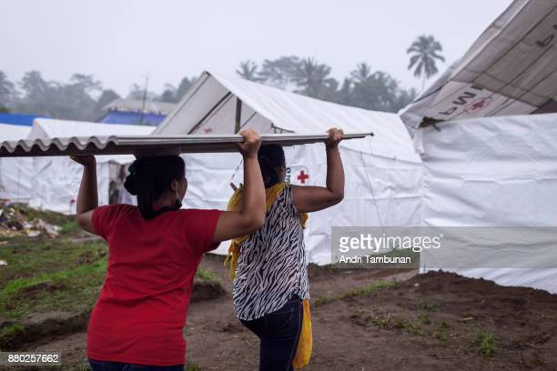 KARANGASEM BALI INDONESIA NOVEMBER 27 Evacuees are seen unloading building material for their temporary shelter at Rendang Evacuation Center on...