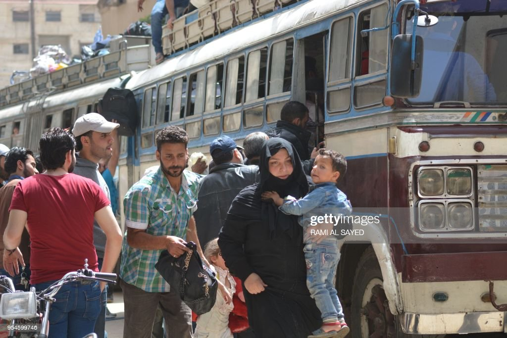 Evacuees board buses with their belongings on top as Syrian rebels and their families were being evacuated from the town of Yalda on the outskirts of Damascus on May 4, 2018, under a negotiated wit...