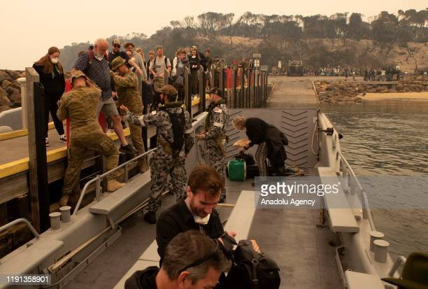 Evacuees board one of HMAS Choules' landing craft at Mallacoota to be ferried out to the ship in Victoria Australia on January 3 2020 The Australian...