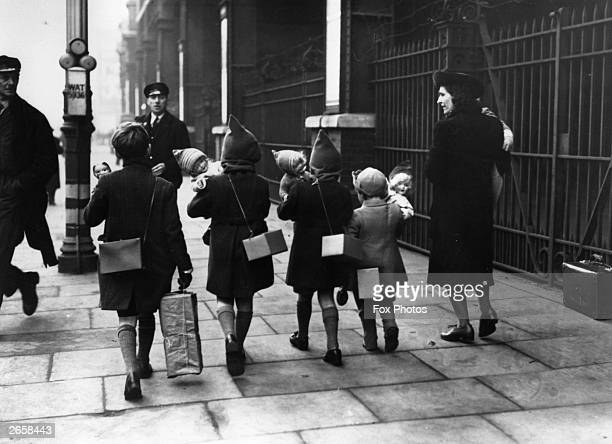 Evacuees complete with Christmas presents and gas masks on their way to Waterloo station to return to the safety of their evacuation areas after...
