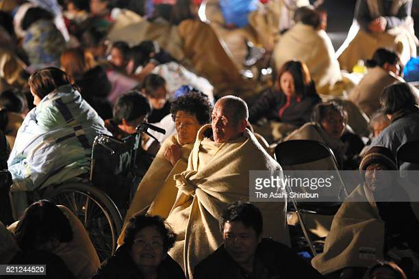 Evacuees cover themselves with blankets at the Mashiki City Hall after the magnitude 64 earthquake jolted on April 15 2016 in Mashiki Kumamoto Japan...