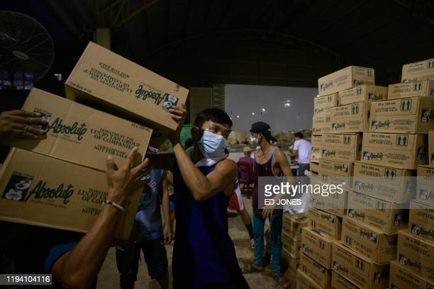 Evacuees displaced following the eruption of the Taal volcano stack boxes of relief supplies at the Bernado Lirio Memorial High School in Tanauan on...