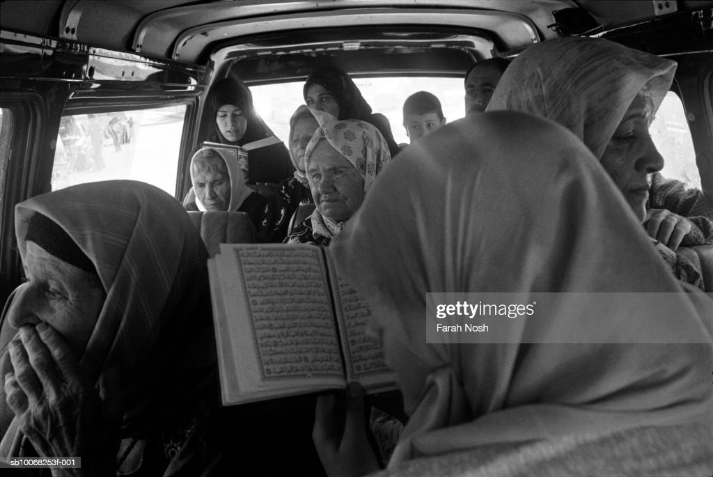 Evacuees from Aitaroun, southern Lebanon, sit in a van, some reading Quran, in what became an emergency shelter at the hospital on August 31, 2006 in Tebnine, Lebanon. Tebnine became a transitional village for those fleeing the southern villages, making their way north to Tyre and Beirut.