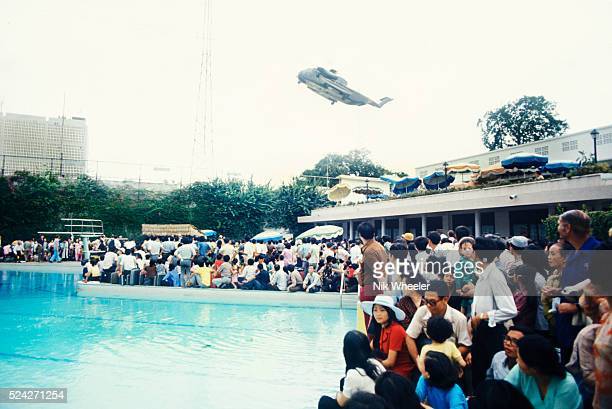 Evacuees inside the US Embassy surround the swimming pool as helicopter rescues stranded civilians trying to escape North Vietnamese troops about to...