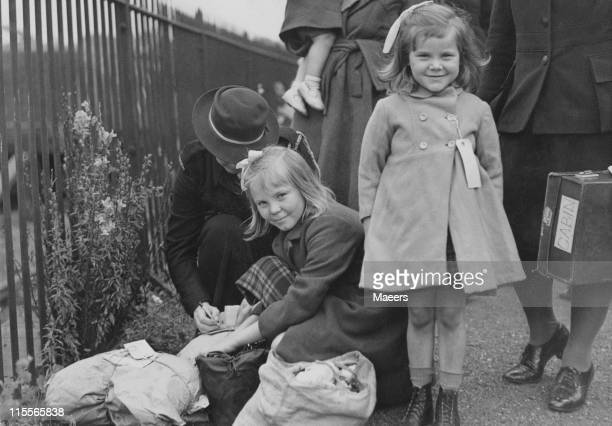Evacuees Jean and Mary Taylor from Uckfield arrive at Cheltenham in Gloucestershire during World War II 29th July 1944 A WVS worker labels their...