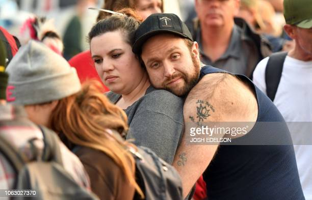Evacuees Jenny Merritt and Austin Wadman wait in line to get a free cell phone at an encampment at a Walmart parking lot in Chico California on...