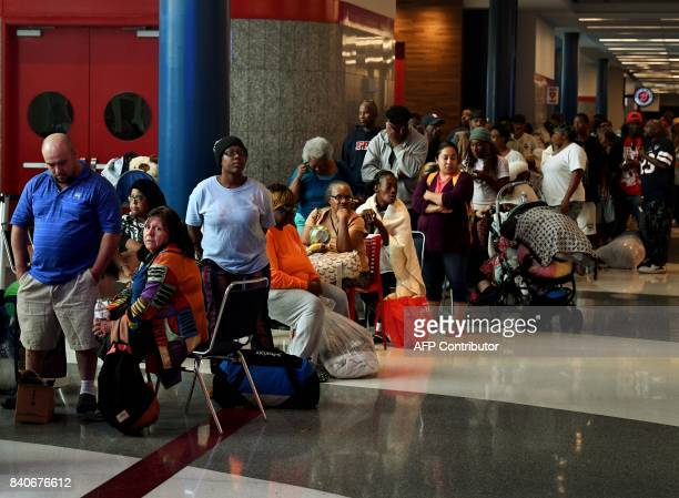 Evacuees line up to apply for FEMA aid at the Convention Center which is housing people from flooded homes after Hurricane Harvey caused heavy...