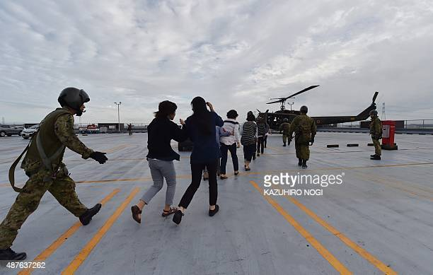 Evacuees prepare to board a military helicopter on the roof of a flooded shopping center in Joso city Ibaraki prefecture on September 11 2015 A...