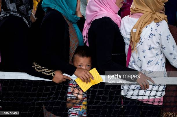 TOPSHOT Evacuees queue for relief goods distributed at an covered basketball court used as an evacuation centre in Baloi Iligan on the southern...