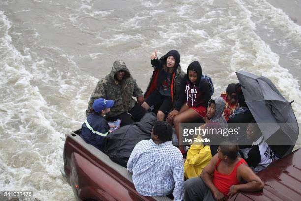 Evacuees ride in the back of a pickup truck after the area was inundated with flooding of Hurricane Harvey on August 30 2017 in Port Arthur Texas...