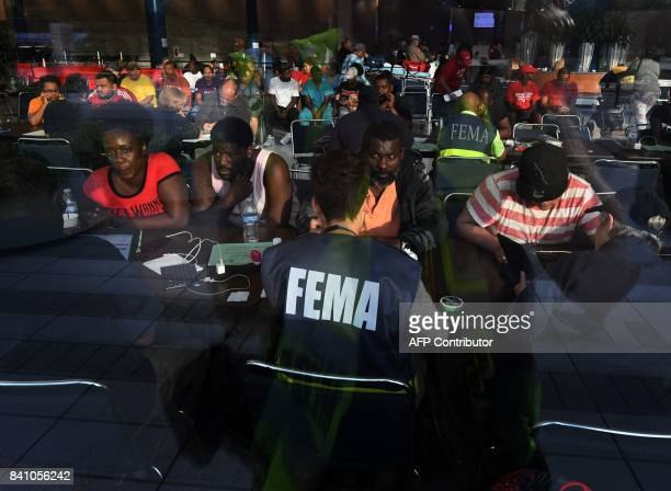 Evacuees seeking financial help consult with FEMA agents at the Convention Center which is serving as an evacuation shelter after Hurricane Harvey...