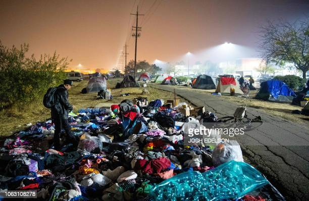 TOPSHOT Evacuees sift through a pile of clothing at an evacuee encampment in a Walmart parking lot in Chico California on November 17 2018 More than...