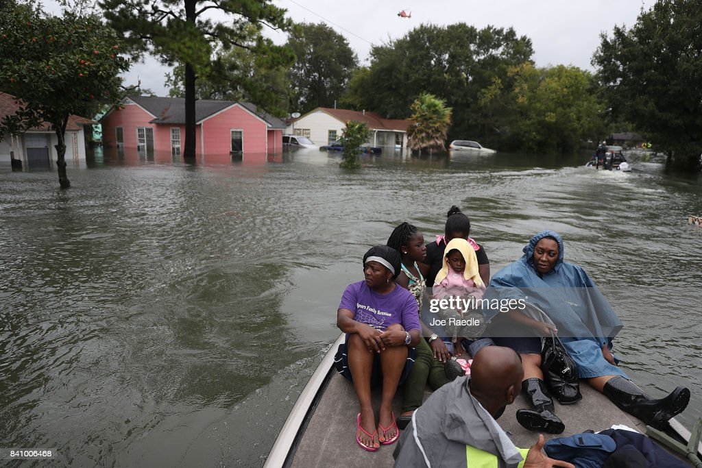 Evacuees sit on a boat after being rescued from flooding from Hurricane Harvey on August 30, 2017 in Port Arthur, Texas. Harvey, which made landfall north of Corpus Christi late Friday evening, is expected to dump upwards to 40 inches of rain in Texas over the next couple of days.