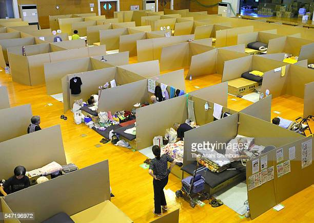 Evacuees spend time at a space separated with cardboards at a temporary housing set up at a gymnasium a day before three months annivsary of the...