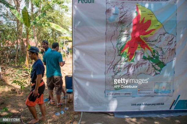 Evacuees stand next to a map of Mount Agung at a shelter in Tembok Buleleng Regency on the Indonesian resort island of Bali on October 1 2017 Mount...