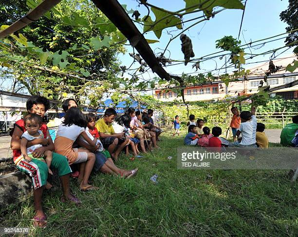 Evacuees take shelter from the heat of the sun under a plant canopy at an evacuation center in Legazpi City Albay province southeast of Manila...