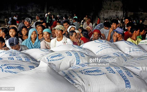 Evacuees wait for the distribution of sacks of rice from the World Food Programme at a warehouse in Pikit town on August 13, 2008 housing hundreds of...