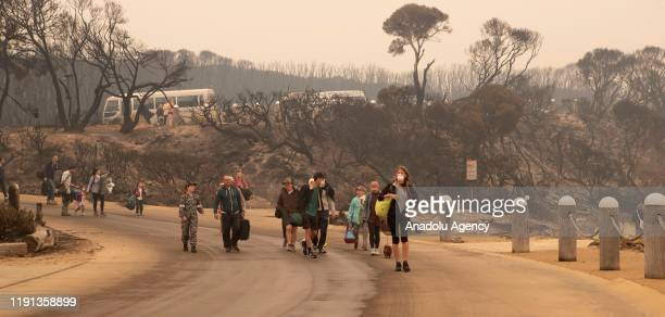Evacuess walk down to the beach at Mallacoota to board vessels and be ferried out to HMAS Choules in Victoria Australia on January 3 2020 The...