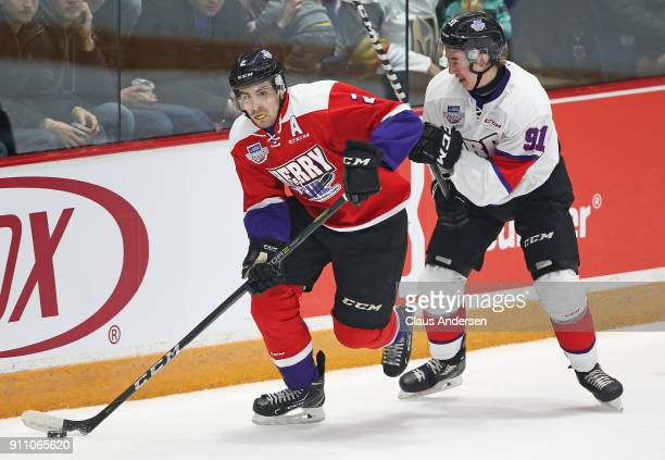 Evan Bouchard of Team Cherry skates with the puck against Ryan McLeod Team Orr in the 2018 SherwinWilliams CHL/NHL Top Prospects game at the Sleeman...