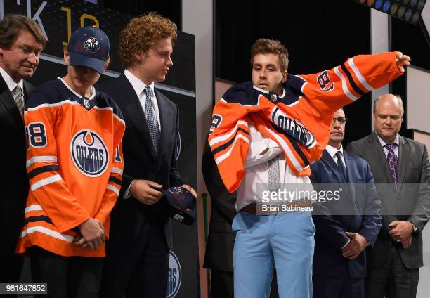 Evan Bouchard puts on his jersey after being selected tenth overall by the Edmonton Oilers during the first round of the 2018 NHL Draft at American...